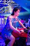 Κορίτσι στη μοτοσικλέτα παιχνιδιών σε ένα arcade Στοκ Φωτογραφίες