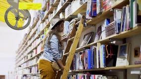 Κορίτσι στη σκάλα που επιλέγει το βιβλίο στα ράφια απόθεμα βίντεο