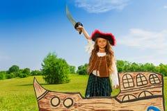 Κορίτσι στη στάση κοστουμιών πειρατών στο σκάφος με το ξίφος Στοκ Εικόνα