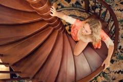 Κορίτσι στη στάση τηβέννων μεταξιού στην ξύλινη σπειροειδή σκάλα στοκ εικόνες με δικαίωμα ελεύθερης χρήσης