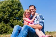 Κορίτσι στη συνεδρίαση περιτυλίξεων dads στο λιβάδι ή στον τομέα Στοκ Εικόνα
