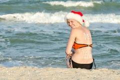 Κορίτσι στη συνεδρίαση Santa στην ακτή και τα γέλια Στοκ Εικόνες