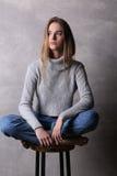 Κορίτσι στη συνεδρίαση πουλόβερ σε μια καρέκλα φραγμών Γκρίζα ανασκόπηση Στοκ Εικόνες