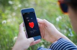κορίτσι στη χλόη που κρατά το smartphone υγείας της Στοκ Εικόνα