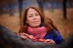 Κορίτσι στις κόκκινες στάσεις μαντίλι στο πάρκο φθινοπώρου στοκ φωτογραφίες
