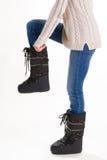 Κορίτσι στις μπότες, τα τζιν και το πουλόβερ χειμερινών φεγγαριών σε ένα άσπρο backgrou Στοκ Φωτογραφίες