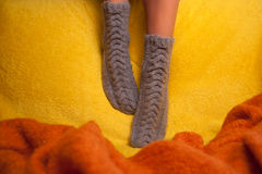 Κορίτσι στις πλεκτές κάλτσες στον καναπέ στοκ φωτογραφία