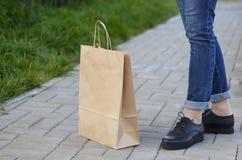 Κορίτσι στις όμορφες στάσεις παπουτσιών δίπλα σε μια τσάντα εγγράφου Στοκ φωτογραφία με δικαίωμα ελεύθερης χρήσης