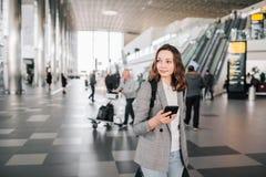 Κορίτσι στον αερολιμένα, που περπατά με το smartphone και τις αποσκευές της στοκ φωτογραφία με δικαίωμα ελεύθερης χρήσης