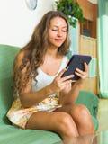 Κορίτσι στον καναπέ με το ereader Στοκ Φωτογραφία