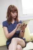 Κορίτσι στον καναπέ που λειτουργεί στην ταμπλέτα στοκ φωτογραφίες