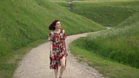 Κορίτσι στον περίπατο φορεμάτων μέσω της αγροτικής πορείας αμμοχάλικου μεταξύ των αναχωμάτων απόθεμα βίντεο