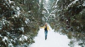 Κορίτσι στους κίτρινους περιπάτους σακακιών γύρω από ένα χειμερινό δάσος που καλύπτεται με το χιόνι απόθεμα βίντεο