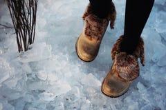 Κορίτσι στους κόκκινους περιπάτους μποτών στον πάγο στοκ εικόνες