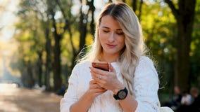 Κορίτσι στο άσπρο μήνυμα γραψίματος πουλόβερ στο smartphone της υπαίθρια Γυναίκα που χρησιμοποιεί την ψηφιακή συσκευή, κύλινδροι  απόθεμα βίντεο