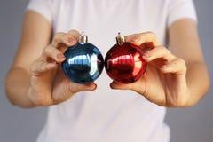 Κορίτσι στο άσπρο παιχνίδι δύο Χριστουγέννων εκμετάλλευσης μπλουζών σφαίρα Κόκκινο, μπλε Στοκ Φωτογραφία