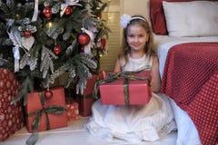 Κορίτσι στο άσπρο φόρεμα στο χριστουγεννιάτικο δέντρο με ένα δώρο στα χέρια Στοκ εικόνες με δικαίωμα ελεύθερης χρήσης