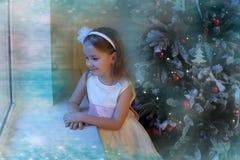 Κορίτσι στο άσπρο φόρεμα στο χριστουγεννιάτικο δέντρο Στοκ Φωτογραφία