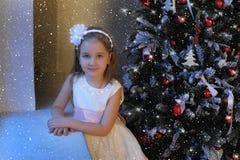 Κορίτσι στο άσπρο φόρεμα στο χριστουγεννιάτικο δέντρο Στοκ Φωτογραφίες