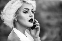 Κορίτσι στο αναδρομικό ύφος που μιλά στο τηλέφωνο Προκλητικός ξανθός με το τηλέφωνο Στοκ Εικόνα