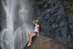 Κορίτσι στο βράχο με το υπόβαθρο καταρρακτών Στοκ φωτογραφία με δικαίωμα ελεύθερης χρήσης