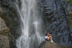Κορίτσι στο βράχο με το υπόβαθρο καταρρακτών Στοκ Φωτογραφία