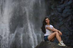 Κορίτσι στο βράχο με το υπόβαθρο καταρρακτών Στοκ φωτογραφίες με δικαίωμα ελεύθερης χρήσης