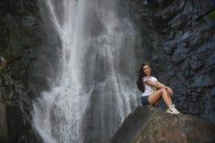 Κορίτσι στο βράχο με το υπόβαθρο καταρρακτών Στοκ Εικόνα