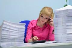 Κορίτσι στο γραφείο μεταξύ των πακέτων των βασίζομαι εγγράφων σε ένα calc στοκ εικόνες με δικαίωμα ελεύθερης χρήσης