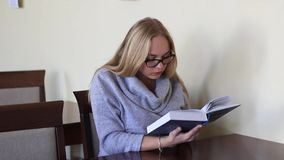 Κορίτσι στο δωμάτιο ανάγνωσης που διαβάζει ένα βιβλίο απόθεμα βίντεο
