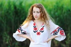 Κορίτσι στο εθνικό ουκρανικό πουκάμισο στο υπόβαθρο χλόης Στοκ φωτογραφία με δικαίωμα ελεύθερης χρήσης