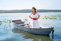 Κορίτσι στο εθνικό φόρεμα στη βάρκα στη λίμνη στοκ εικόνες