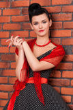 Κορίτσι στο εκλεκτής ποιότητας φόρεμα κοντά στο τουβλότοιχο Στοκ φωτογραφία με δικαίωμα ελεύθερης χρήσης