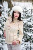 Κορίτσι στο θερμό μάλλινο πουλόβερ κάτω από τους χιονισμένους κλάδους δέντρων στοκ εικόνα