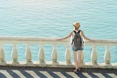 Κορίτσι στο καπέλο που στέκεται στο μπαλκόνι και που εξετάζει τη θάλασσα μπακαράδων στοκ φωτογραφία με δικαίωμα ελεύθερης χρήσης