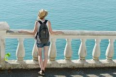Κορίτσι στο καπέλο που στέκεται στο μπαλκόνι και που εξετάζει τη θάλασσα μπακαράδων στοκ φωτογραφία