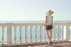 Κορίτσι στο καπέλο που στέκεται στα σκαλοπάτια και που εξετάζει τη θάλασσα μπακαράδων στοκ εικόνες