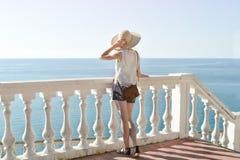 Κορίτσι στο καπέλο που στέκεται στα σκαλοπάτια και που εξετάζει τη θάλασσα μπακαράδων στοκ φωτογραφία