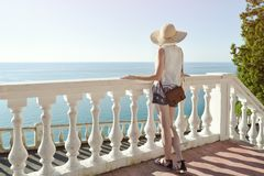 Κορίτσι στο καπέλο που στέκεται στα σκαλοπάτια και που εξετάζει τη θάλασσα μπακαράδων στοκ εικόνα με δικαίωμα ελεύθερης χρήσης