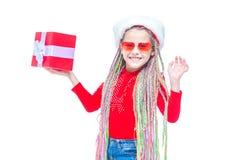 Κορίτσι στο καπέλο santa ` s Το πορτρέτο λίγου χαριτωμένου κιβωτίου εκμετάλλευσης κοριτσιών του χριστουγεννιάτικου δώρου, μικρό κ στοκ εικόνες με δικαίωμα ελεύθερης χρήσης