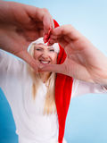 Κορίτσι στο καπέλο Άγιου Βασίλη που κάνει το σύμβολο καρδιών με τα δάχτυλα Στοκ Εικόνα