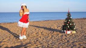 Κορίτσι στο κοστούμι στο νέο θέρετρο στην παραλία με τα δώρα 1 απόθεμα βίντεο