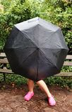 Κορίτσι στο κρύψιμο πάγκων πίσω από την ομπρέλα στοκ εικόνα