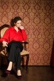 Κορίτσι στο κόκκινο αρσενικό πουκάμισο. Στο αναδρομικό εσωτερικό στοκ φωτογραφία