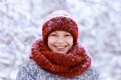 Κορίτσι στο κόκκινο καπέλο και ένα μαντίλι που έχει τη διασκέδαση στο χειμερινό πάρκο στοκ φωτογραφία με δικαίωμα ελεύθερης χρήσης