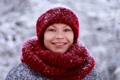 Κορίτσι στο κόκκινο καπέλο και ένα μαντίλι που έχει τη διασκέδαση στο χειμερινό πάρκο στοκ εικόνα με δικαίωμα ελεύθερης χρήσης
