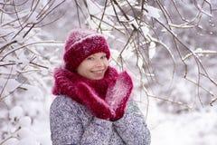 Κορίτσι στο κόκκινο καπέλο και ένα μαντίλι που έχει τη διασκέδαση στο χειμερινό πάρκο στοκ εικόνες