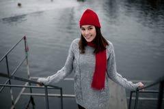 Κορίτσι στο κόκκινο καπέλο και μαντίλι που περπατά στο χειμερινό πάρκο κοντά στη λίμνη Στοκ εικόνες με δικαίωμα ελεύθερης χρήσης