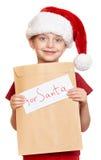 Κορίτσι στο κόκκινο καπέλο με την επιστολή στο santa - έννοια Χριστουγέννων χειμερινών διακοπών Στοκ Φωτογραφίες