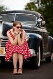 Κορίτσι στο κόκκινο με το εκλεκτής ποιότητας αυτοκίνητο Στοκ Φωτογραφίες